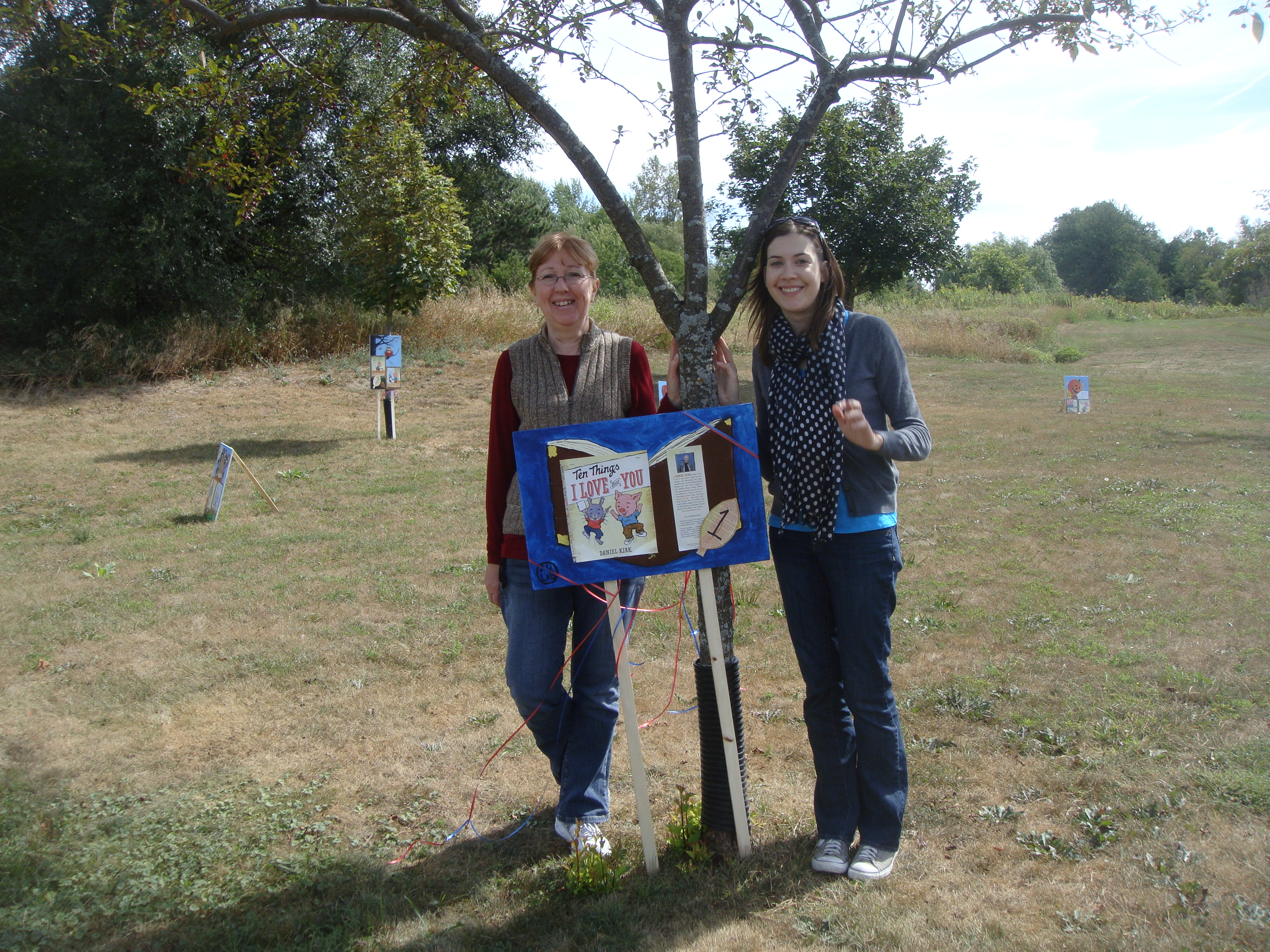 cassie-banaszak-and-jane-walsh-pose-by-a-storyboard-at-booktoberfest